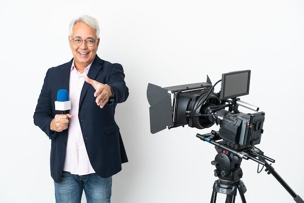 Репортер среднего возраста бразильский мужчина держит микрофон и сообщает новости на белом фоне, пожимая руку для заключения хорошей сделки