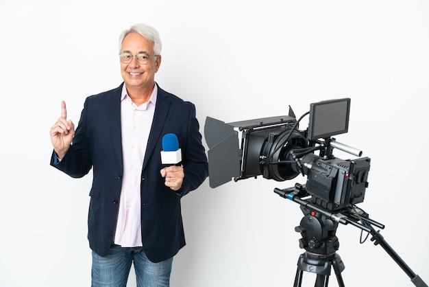 Репортер среднего возраста бразильский мужчина держит микрофон и сообщает новости на белом фоне, показывая и поднимая палец в знак лучших