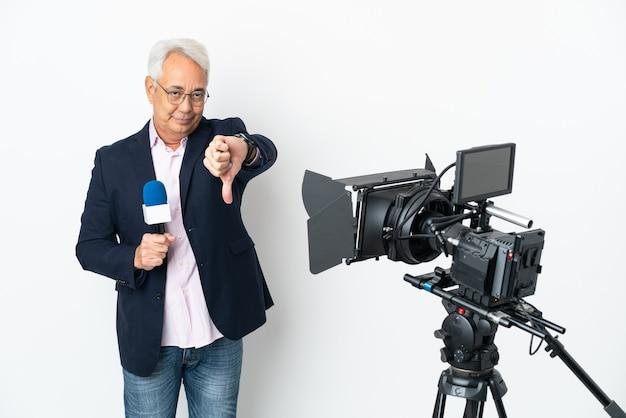 レポーター中年ブラジル人男性がマイクを持って、否定的な表現で親指を下に示す白い背景で隔離のニュースを報告します