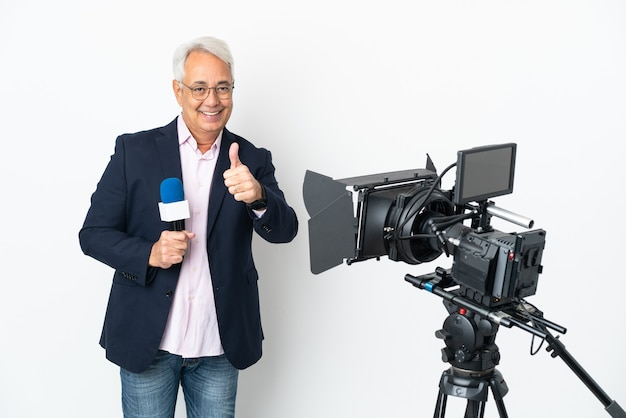 Репортер среднего возраста бразильский мужчина держит микрофон и сообщает новости на белом фоне с большими пальцами руки вверх, потому что произошло что-то хорошее