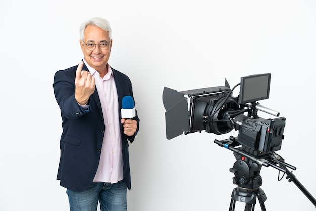 Репортер среднего возраста бразильский мужчина держит микрофон и сообщает новости, изолированные на белой стене, делая приближающийся жест