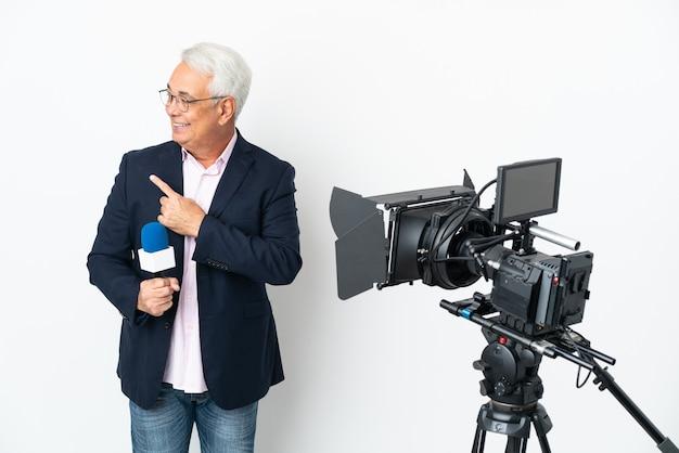 Репортер среднего возраста бразильский мужчина держит микрофон и сообщает новости, изолированно указывая в сторону, чтобы представить продукт Premium Фотографии