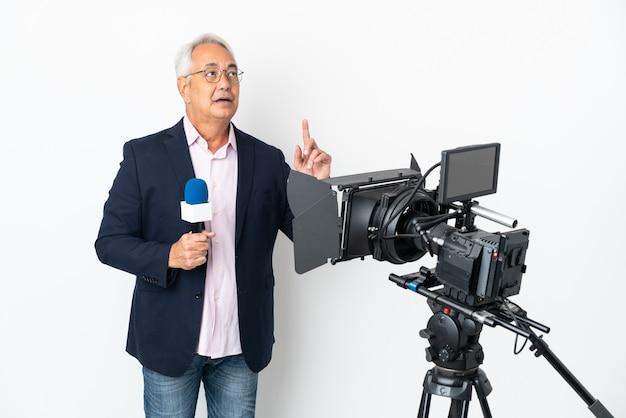 Репортер среднего возраста бразильский мужчина держит микрофон и сообщает новости изолированно, думая об идее, указывая пальцем вверх