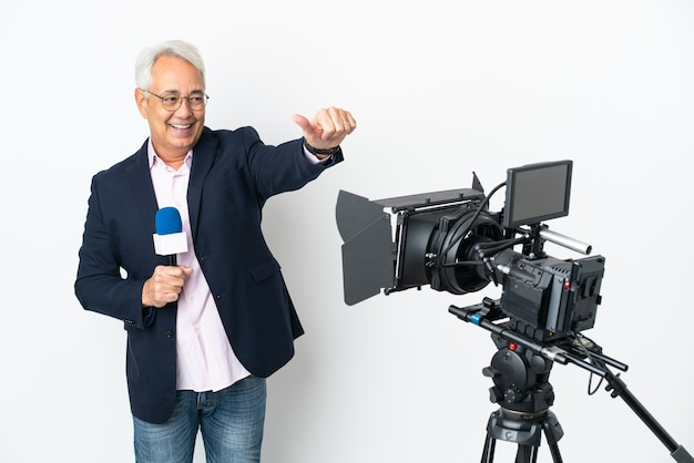 Reporter middle age brazilian man holding a microphone and reporting news isolated on white background giving a thumbs up gesture