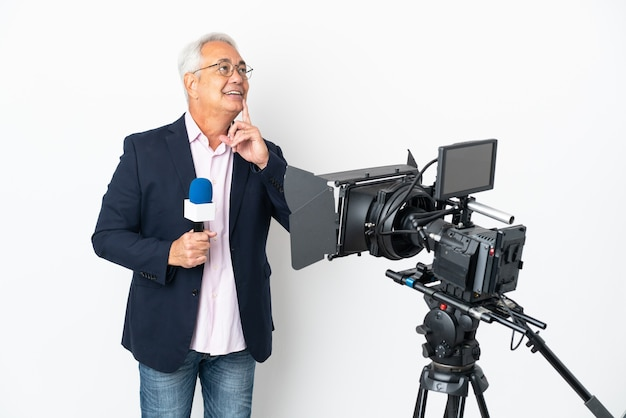Reporter middle age brazilian man holding a microphone and reporting news isolated on white background thinking an idea while looking up