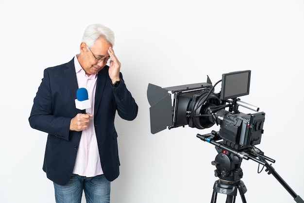 Reporter middle age brazilian man holding a microphone and reporting news isolated on white background with headache