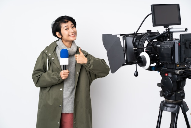 Reporter vietnamese woman holding a microphone and reporting news giving a thumbs up gesture