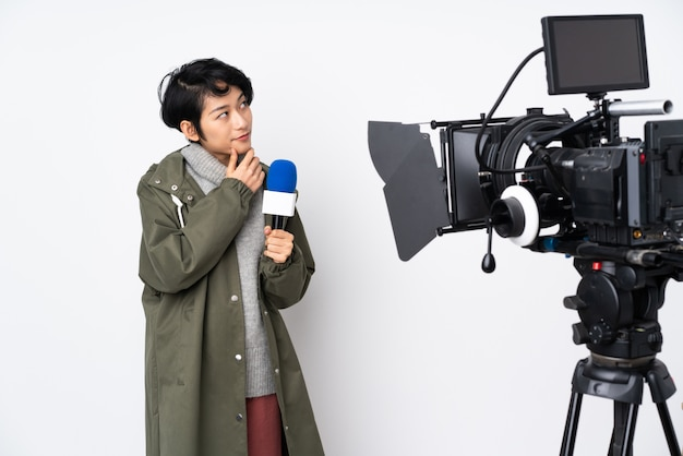 Reporter vietnamese woman holding a microphone and reporting news having doubts and with confused face expression