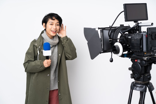 Reporter vietnamese woman holding a microphone and reporting news listening to something by putting hand on the ear