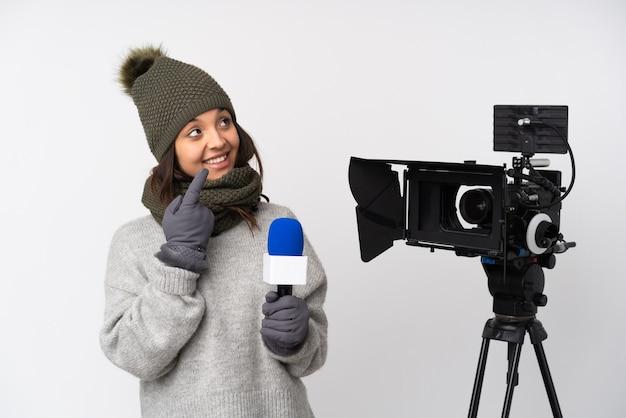 マイクを持って人差し指で孤立した白いポインティングに関するニュースを報告するレポーターの女性は素晴らしいアイデアです