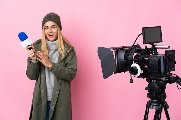 Женщина-репортер держит микрофон и сообщает новости над изолированными розовыми аплодисментами после презентации на конференции