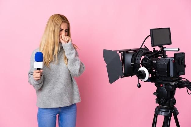 マイクを持っていると多くの咳をして孤立したピンクの上のニュースを報告するレポーター女性