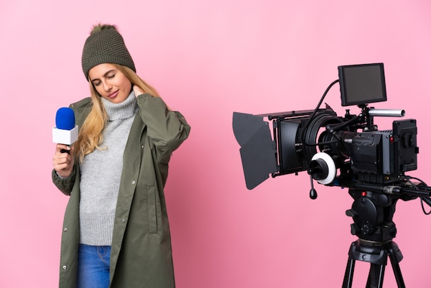 マイクを持って、首の痛みで孤立したピンクの壁にニュースを報告するレポーターの女性