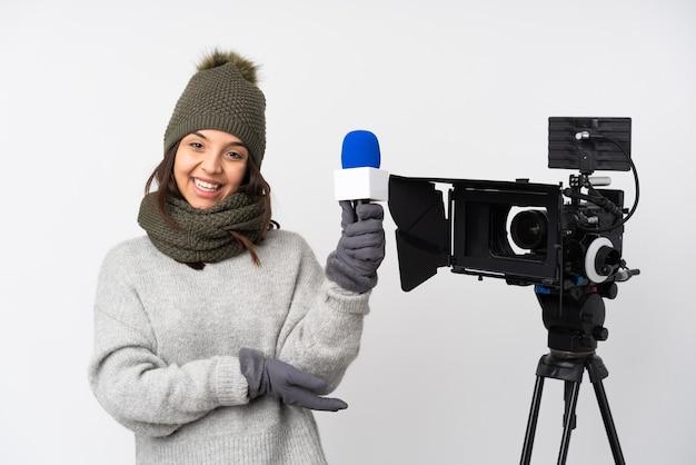 Женщина-репортер держит микрофон и сообщает новости на изолированном белом фоне, протягивая руки в сторону, приглашая приехать