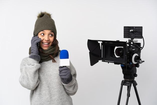 マイクを持って、持ち帰り用のコーヒーと携帯電話を持っている孤立した白い背景の上のニュースを報告するレポーターの女性