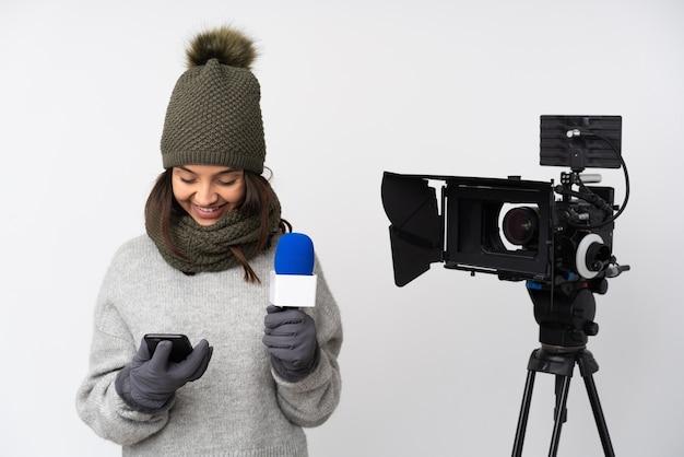 マイクを持って、持ち帰り用のコーヒーと携帯電話を保持している孤立した白い背景の上のニュースを報告するレポーターの女性