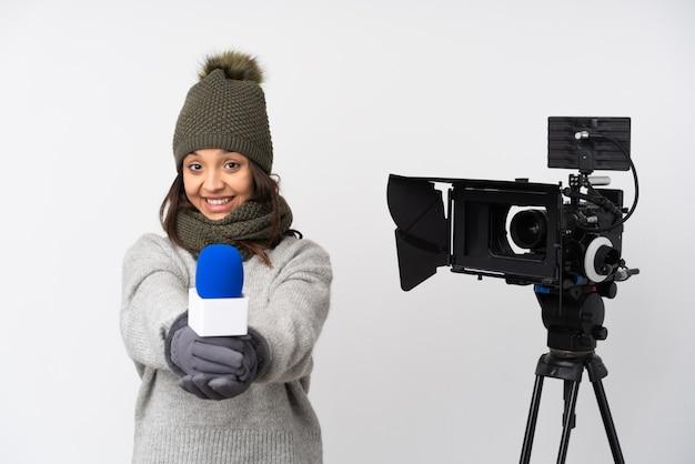 Женщина-репортер держит микрофон и сообщает новости на изолированном белом фоне, держа на ладони воображаемое пространство для вставки рекламы