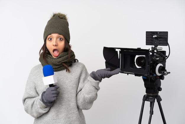 マイクを持って、電話のジェスチャーをし、疑う孤立した白い背景の上のニュースを報告するレポーターの女性