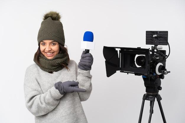 Репортер женщина держит микрофон и сообщает новости на изолированном белом фоне, указывая пальцем в сторону и представляет продукт