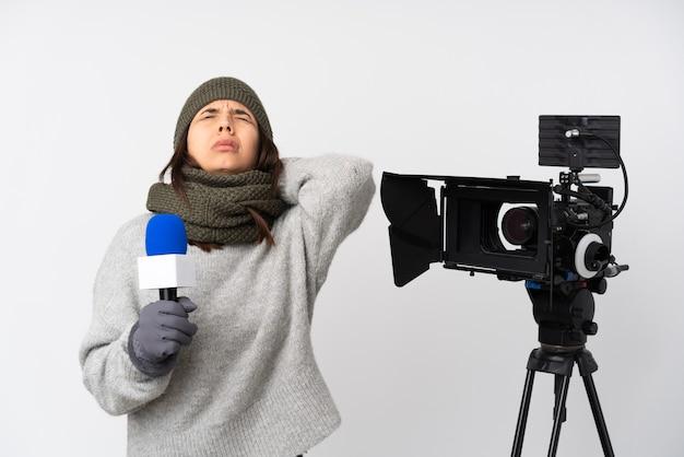 マイクを保持し、首の痛みと孤立した白い背景の上のニュースを報告するレポーターの女性