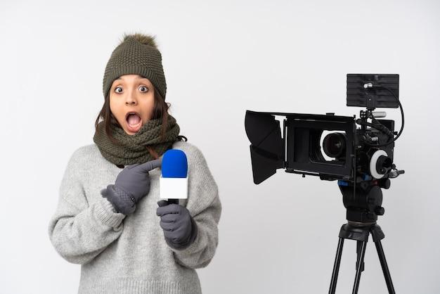 マイクを持って、孤立した白い壁を越えてニュースを報告するレポーターの女性は驚いて、側を指しています