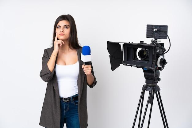마이크를 잡고 아이디어를 생각하는 격리 된 흰 벽에 뉴스를보고 기자 여자