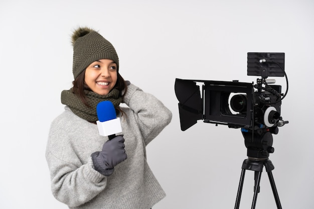 Репортер женщина держит микрофон и сообщает новости над изолированной белой стеной, думая об идее