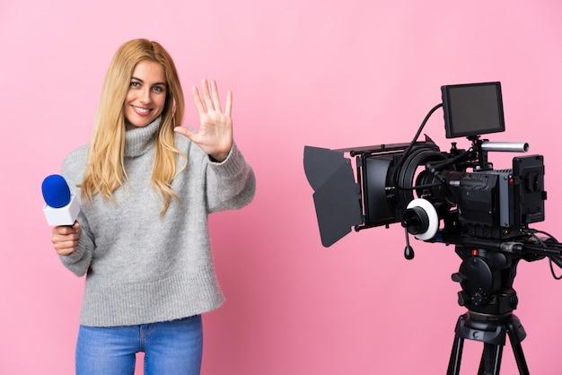 マイクを持っていると指で5を数えるピンクの壁にニュースを報告しているレポーターの女性