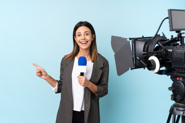 Reporter woman holding a microphone and reporting news over  blue wall pointing finger to the side