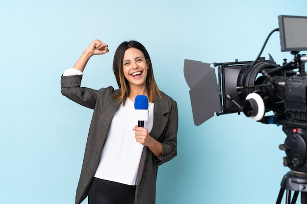 Reporter woman holding a microphone and reporting news over isolated blue wall celebrating a victory