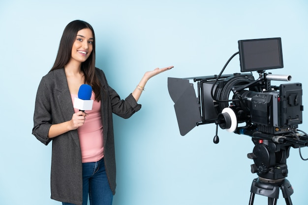 Reporter woman holding a microphone and reporting news isolated on blue wall extending hands to the side for inviting to come