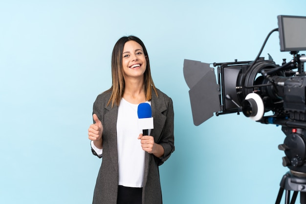 Reporter woman holding a microphone and reporting news over isolated blue wall giving a thumbs up gesture