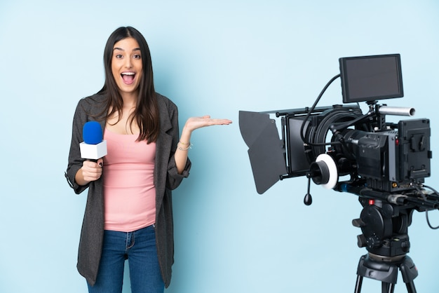 Reporter woman holding a microphone and reporting news isolated on blue wall with shocked facial expression