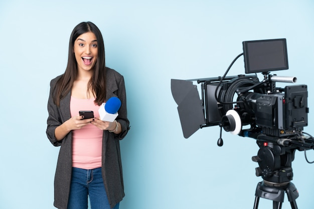 Reporter woman holding a microphone and reporting news isolated on blue