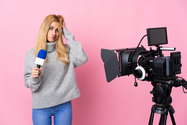 Reporter woman holding a microphone and reporting news over isolated pink having doubts