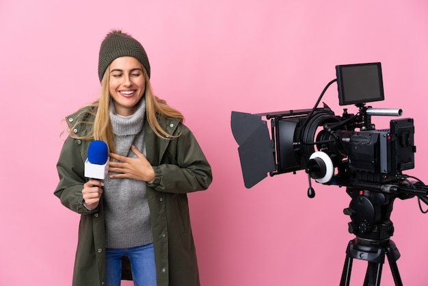 Reporter woman holding a microphone and reporting news over isolated pink smiling a lot