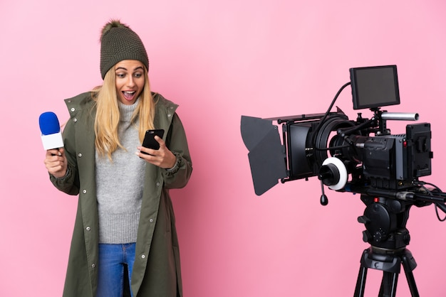 Reporter woman holding a microphone and reporting news over isolated pink surprised and sending a message