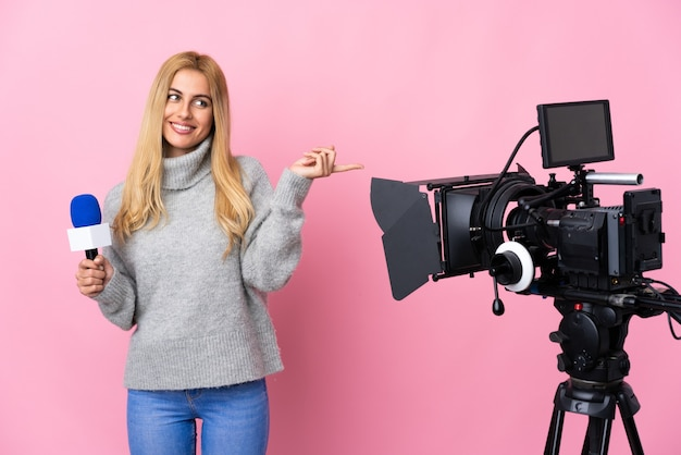 Reporter woman holding a microphone and reporting news over isolated pink wall holding copyspace imaginary on the palm to insert an ad