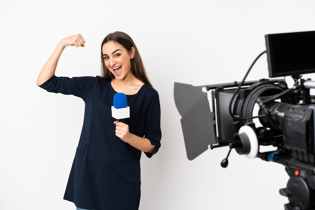 Reporter woman holding a microphone and reporting news isolated on white doing strong gesture