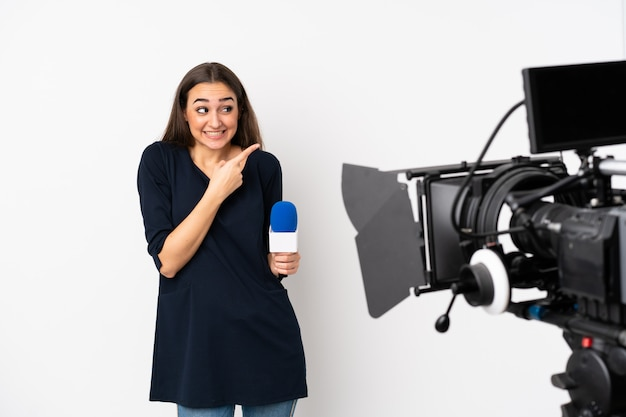 Reporter woman holding a microphone and reporting news isolated on white frightened and pointing to the side