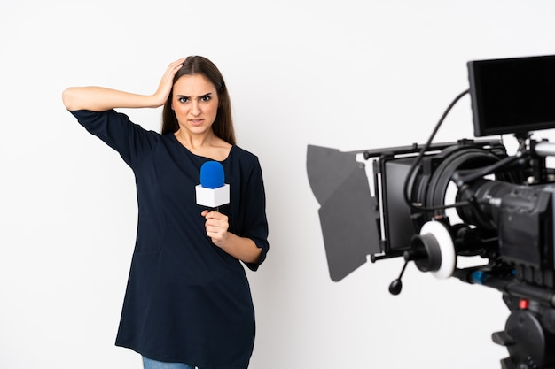 Reporter woman holding a microphone and reporting news isolated on white frustrated and takes hands on head