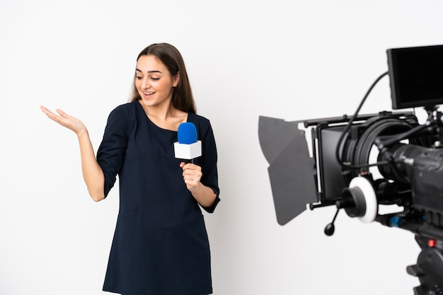 Reporter woman holding a microphone and reporting news isolated on white holding copyspace with two hands