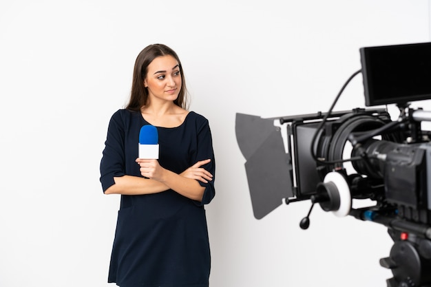 Reporter woman holding a microphone and reporting news isolated on white portrait