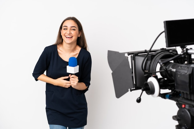 Reporter woman holding a microphone and reporting news isolated on white smiling a lot