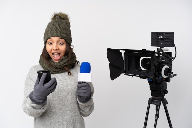 Reporter woman holding a microphone and reporting news over isolated white wall holding coffee to take away and a mobile
