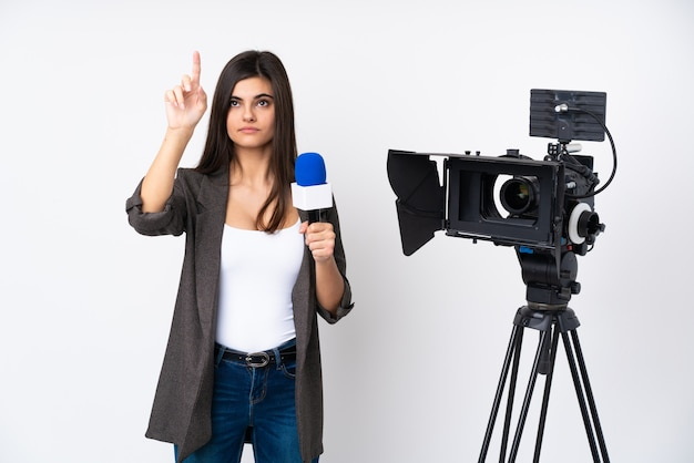Reporter woman holding a microphone and reporting news over isolated white wall touching on transparent screen