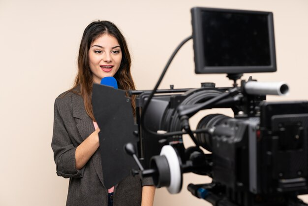 Reporter woman holding a microphone and reporting news over isolated white wall