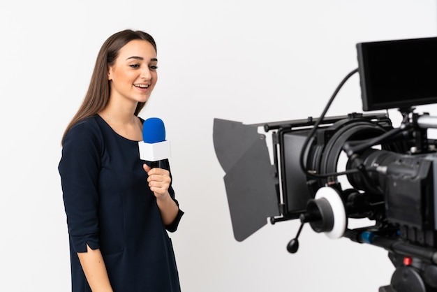 Reporter woman holding a microphone and reporting news isolated on white