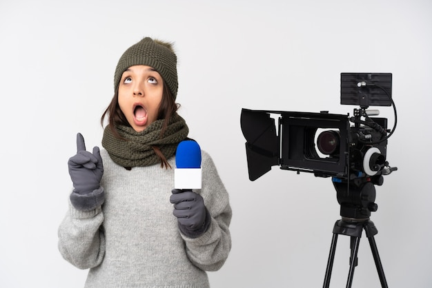 Reporter woman holding a microphone and reporting news isolated