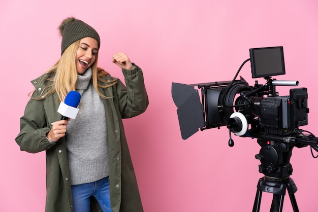 Reporter woman holding a microphone and reporting news over pink wall celebrating a victory